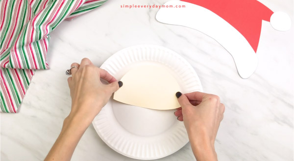 hands gluing face to paper plate Santa craft