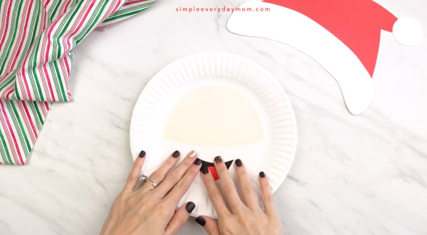 hands gluing mouth onto Santa paper plate craft