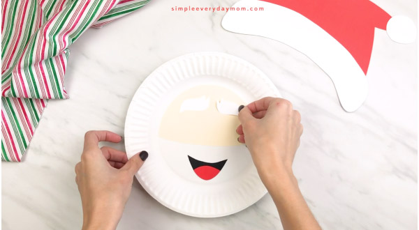 hands gluing eyebrows onto Santa paper plate craft