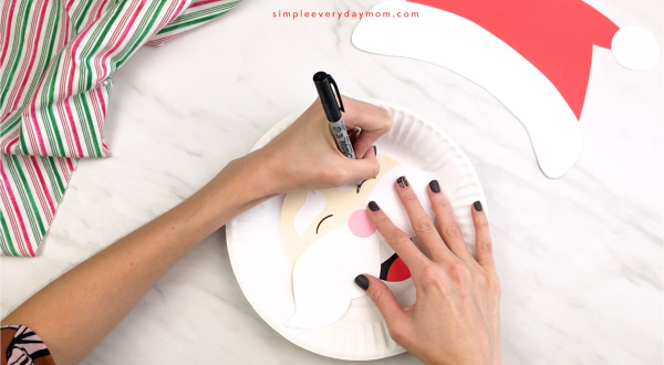 hands drawing eyes on paper plate Santa craft