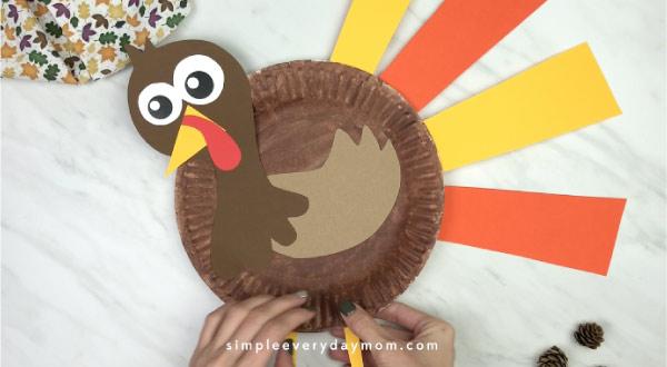 hands gluing feet onto paper plate turkey craft