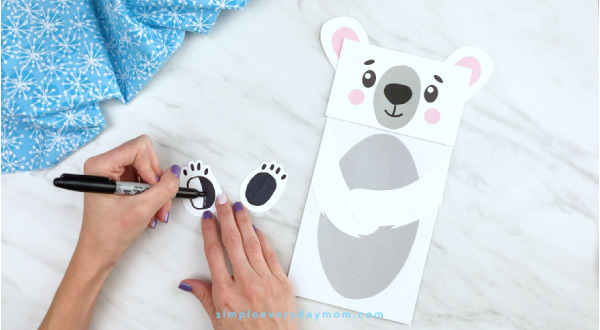 Hands drawing on polar bear footpads