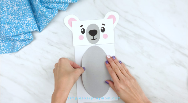 Hands gluing belly to paper bag polar bear craft