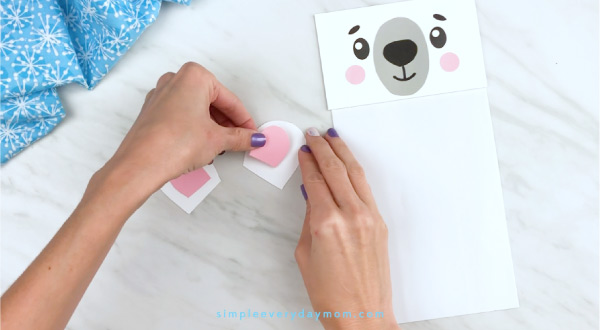 Hands gluing inner ear to polar bear craft
