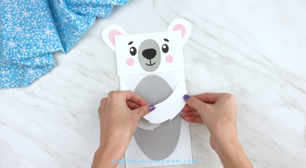 Hands gluing arms to paper bag polar bear craft