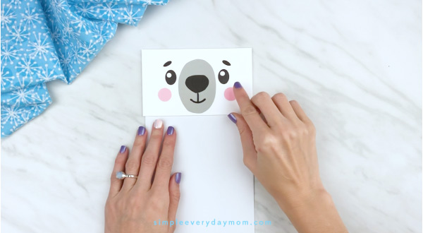 Hands gluing cheeks to polar bear craft template