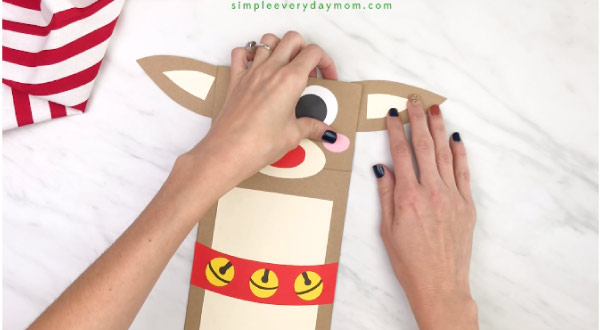 hand gluing ears onto paper bag reindeer craft