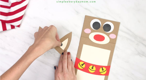 hands gluing paper reindeer ears together