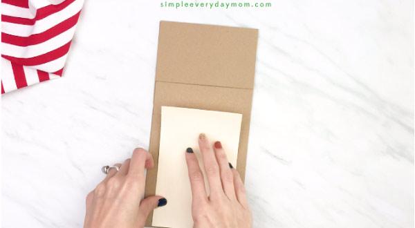 hand gluing belly onto paper beg reindeer craft