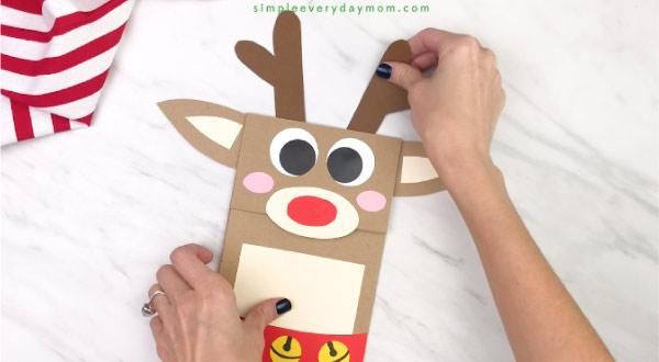 hand gluing antlers onto paper bag reindeer craft