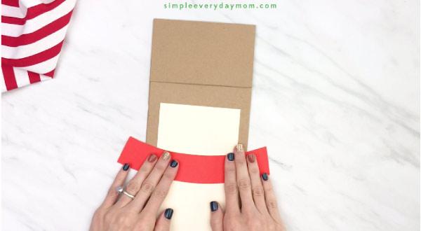 hand gluing harness onto paper beg reindeer craft