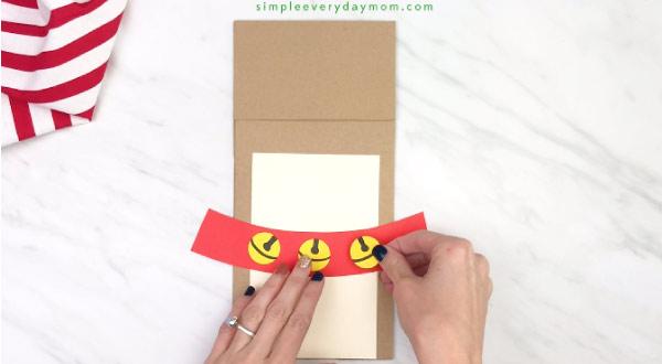 hand gluing bells onto paper beg reindeer craft