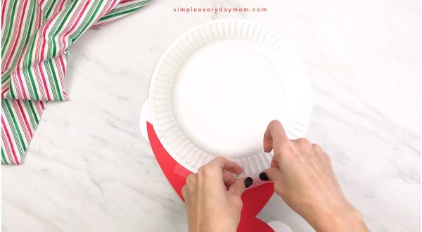 hands taping paper Santa hat onto Santa paper plate craft