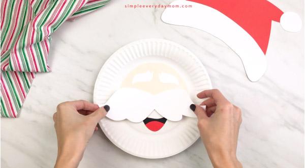 hands gluing mustache onto Santa paper plate craft