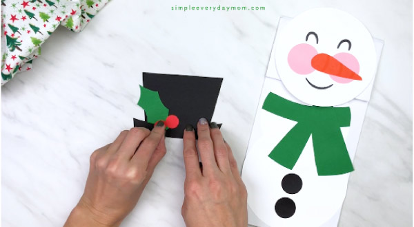 Hands gluing paper holly onto snowman hat