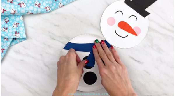 Hands gluing scarf piece onto paper plate snowman
