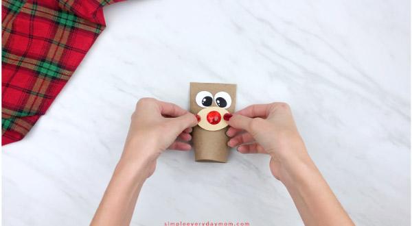 hands gluing nose onto toilet paper roll reindeer craft