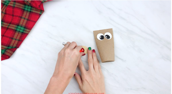 hands gluing red nose onto toilet paper roll reindeer muzzle