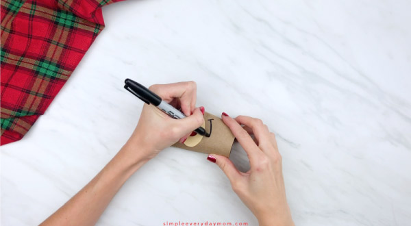 hands drawing mouth onto toilet paper roll reindeer craft