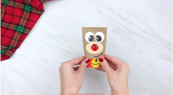 hands gluing harness onto toilet paper roll reindeer craft