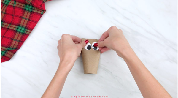 hands gluing eyes onto toilet paper roll reindeer craft