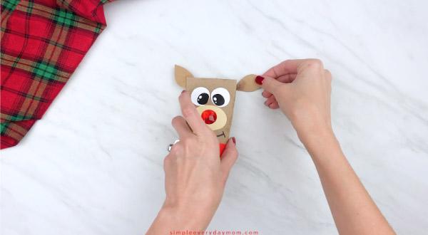 hands gluing ears onto toilet paper roll reindeer craft
