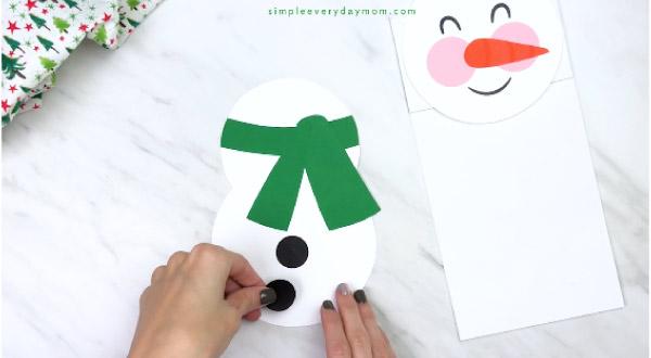 Hands gluing black circles onto paper bag snowman body