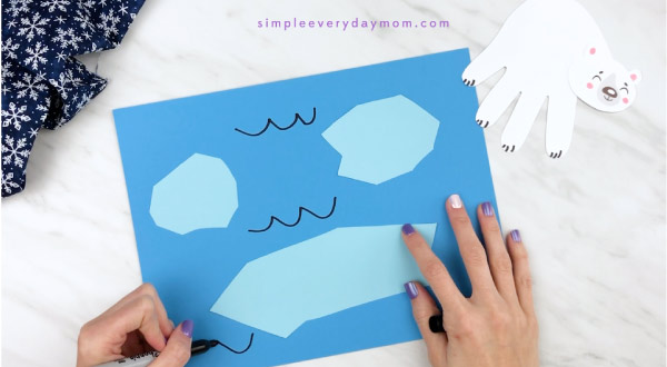 Hands drawing water marks onto blue paper