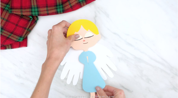 Hands gluing angel body onto handprint angel wings