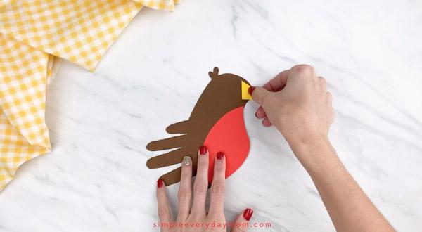 hands gluing beak onto handprint robin