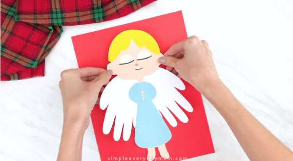 Hands gluing handprint angel to red paper