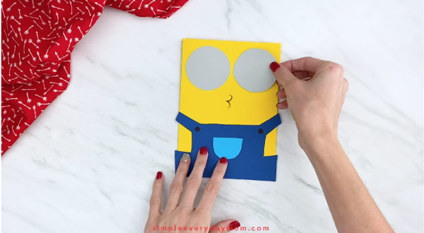 Hands gluing minion goggles onto card