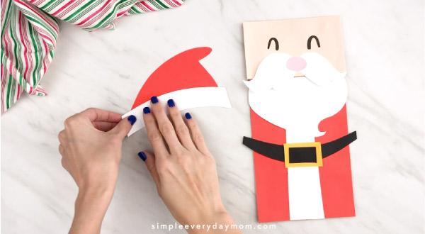 Hands gluing Santa hat together