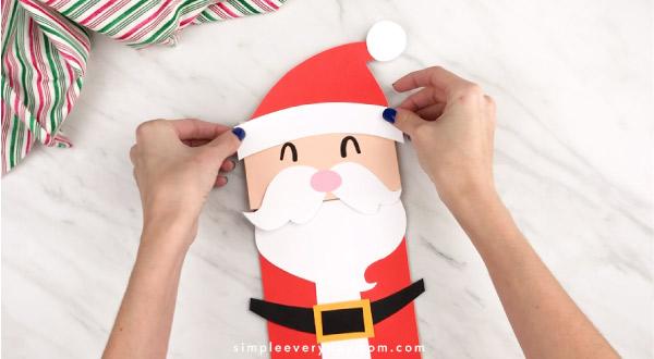 Hands gluing Santa hat to paper bag Santa craft