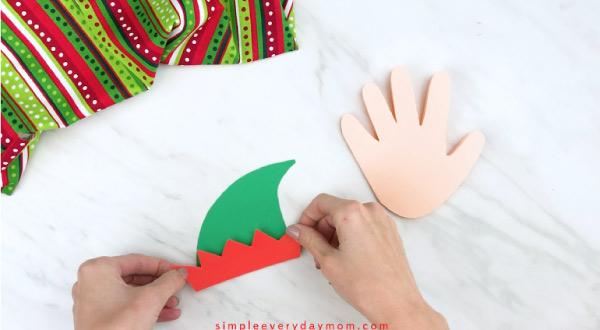Hands gluing elf hat bottom on hat base