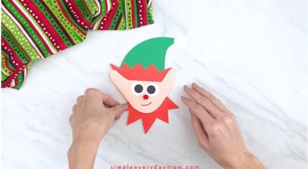 Hands gluing elf neck frill onto handprint elf craft