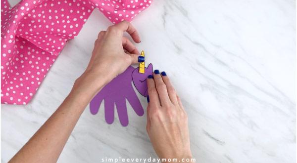 Hands gluing unicorn horn onto handprint unicorn
