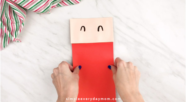 Hands gluing red paper to paper bag Santa