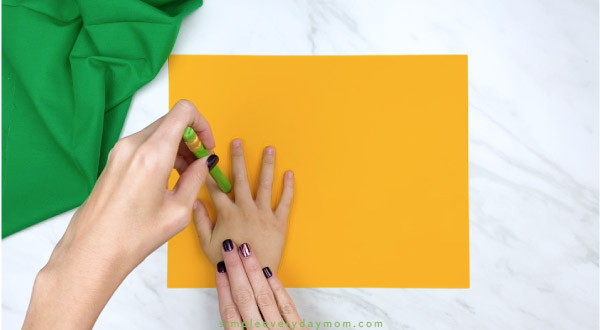 Adult hand trace child hand onto yellow paper