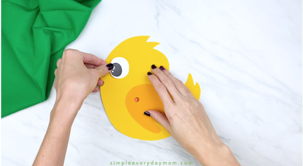 Hands gluing eye to handprint chick craft
