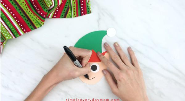 Hands drawing smile on handprint elf