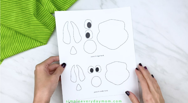 hands holding dinosaur craft template