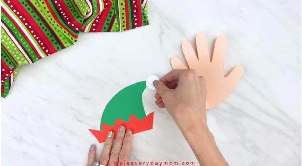 Hands gluing white puff onto elf hat craft