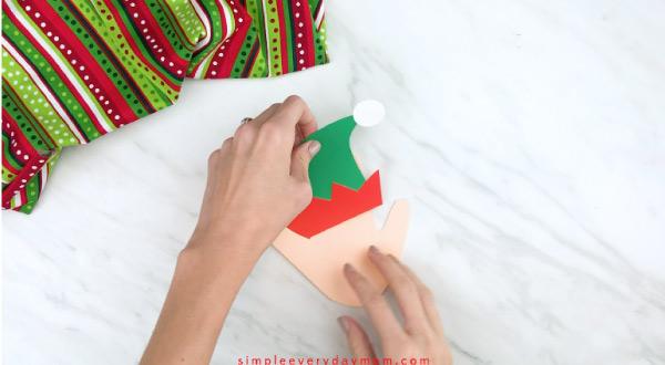 Hands gluing elf hat onto handprint craft
