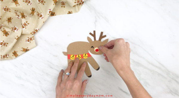 Hands gluing head onto handprint reindeer body