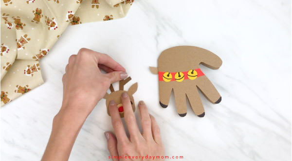 Hands gluing antlers onto handprint reindeer head