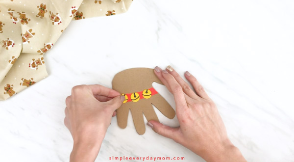 Hands gluing bells onto handprint reindeer card craft