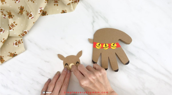 Hands gluing muzzle onto handprint reindeer face