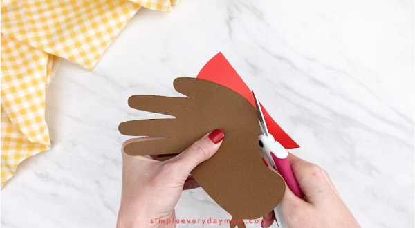 hands cutting red paper
