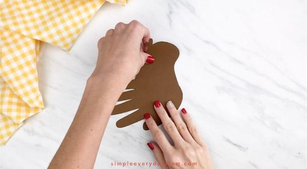 hands gluing head onto handprint robin craft
